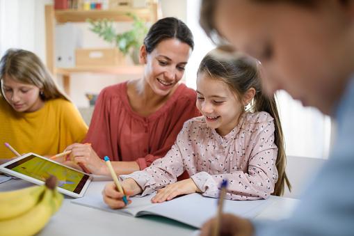 Group of homeschooling children with parent teacher studying indoors, coronavirus concept.