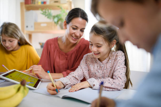 Group of homeschooling children with teacher studying indoors, coronavirus concept. stock photo