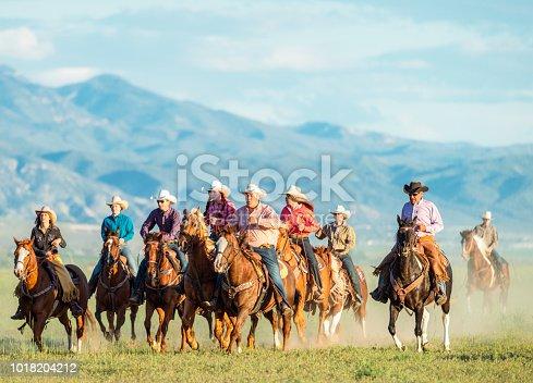 Mountain ranges behind a group of men and women on horseback in rural Utah, USA.