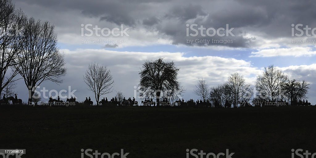 Group of horsemen silhouetted against evening sky stock photo
