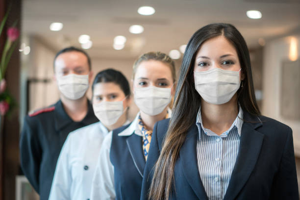 Group of hotel workers wearing facemask stock photo