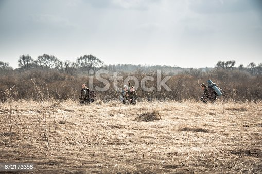 istock Group of hunters hiding in rural field with dry grass during hunting season in overcast day 672173358