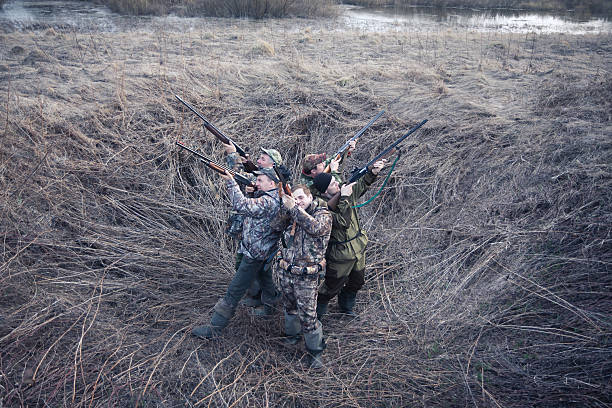 Group of hunters standing back to back in rural field Group of hunters standing back to back in rural field and aiming and prepared to make a shot. Concept for teamwork. bird hunting stock pictures, royalty-free photos & images