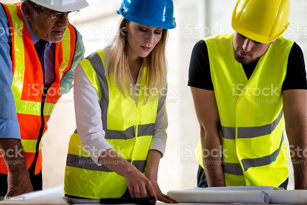 Group of industrial engineers and investor with computer outdoor stock photo
