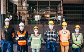 Group of industrial or engineer corporate workers wear protective mask and hard hat helmet standing line up in front of factory lock down prevention for Coronavirus or COVID-19 epidemic outbreak