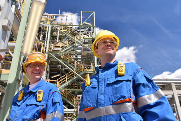group of industrial workers in a refinery - oil processing equipment and machinery stock photo