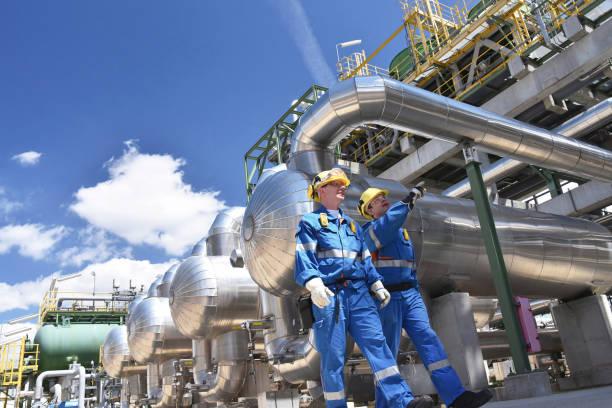 grupa pracowników przemysłowych w rafinerii - urządzenia i maszyny do przetwórstwa ropy naftowej - kask ochronny odzież ochronna zdjęcia i obrazy z banku zdjęć