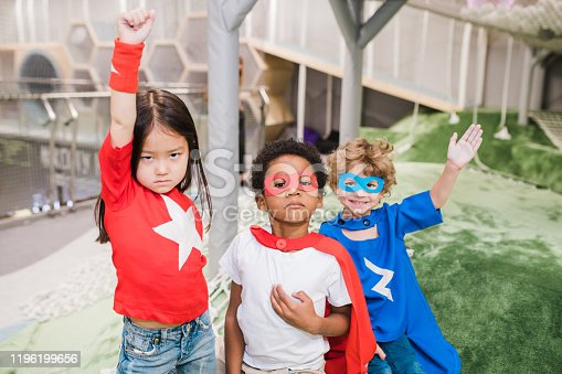 Group of intercultural children in attire of superheroes standing in front of camera during play in kindergarten
