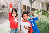 Group of intercultural children in attire of superheroes standing in front of camera during play in kindergarten