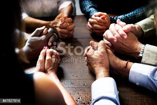 847516586 istock photo Group of interlocked fingers praying together 847527514