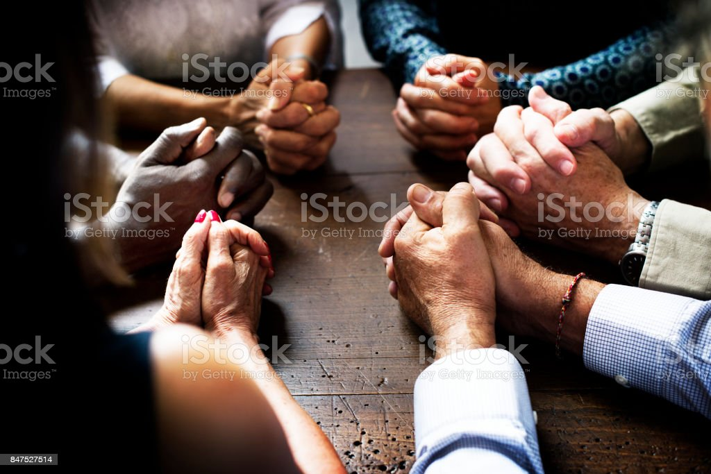 Group of interlocked fingers praying together stock photo