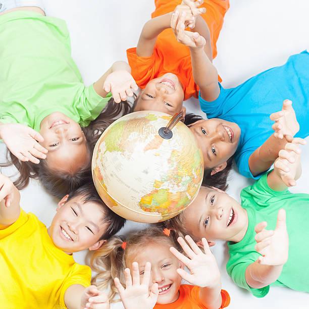 Grupo de divertido internacional niños con globo de tierra - foto de stock