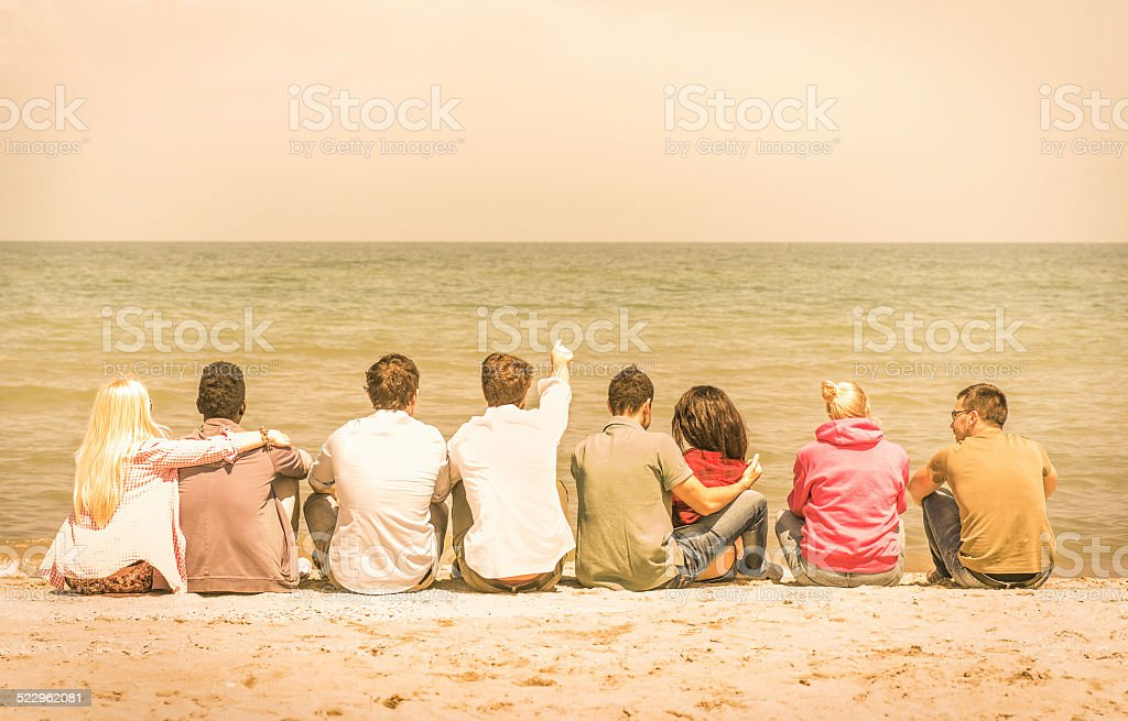 Group of international multiracial friends sitting at the beach stock photo