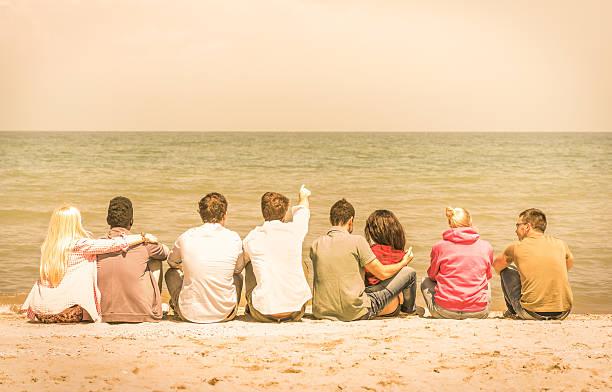 Grupo de international multirracial amigos sentado na praia - foto de acervo