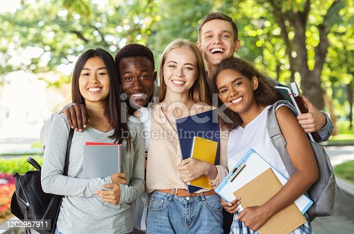 Group of international happy students with books and notebooks having fun in park after studying, smiling at camera