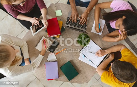 istock Group of international students sitting at table, top view 1178550125