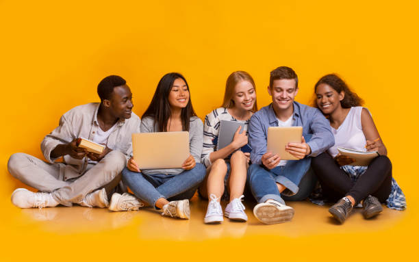Group of international students studying for university exams Group of multiracial students studying for university exams, sitting on floor, using laptop, digital tablet, holding books, yellow background teenagers only stock pictures, royalty-free photos & images