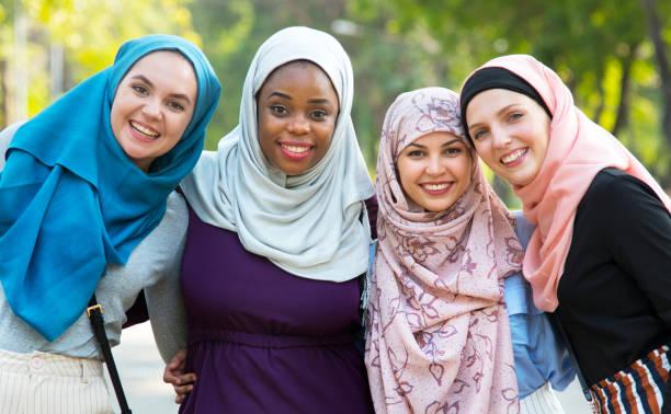 group of islamic friends embracing and smiling together - скромная одежда стоковые фото и изображения