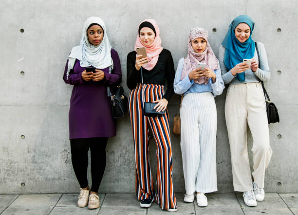 group of islamic girls using smart phone - arabic girl stock photos and pictures