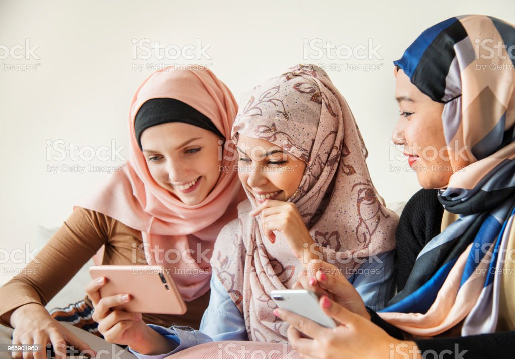 Group of islamic women talking and watching on the phone together - Royalty-free Addict Stock Photo