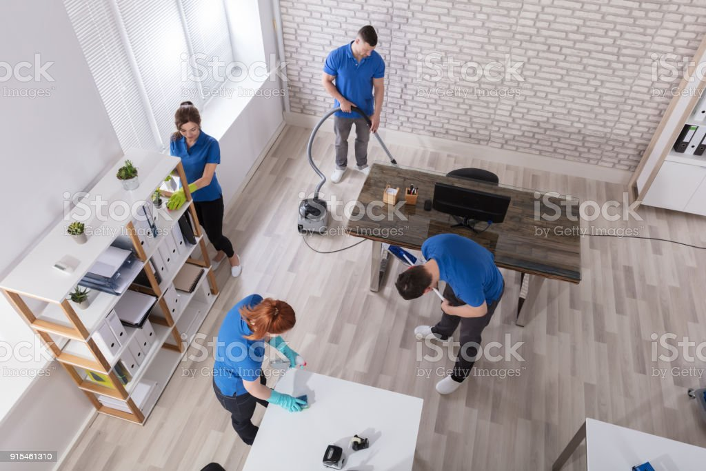 Group Of Janitors Cleaning The Office stock photo