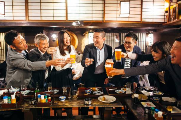 居酒屋日本居酒屋でお祝いのトーストを食べる日本人グループ - 親睦会 ストックフォトと画像