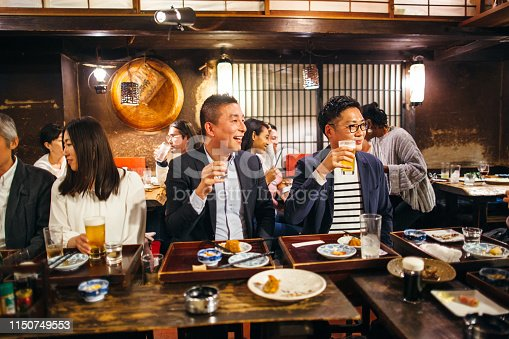 A group of Japanese people are talking while drinking alcohol in an Izakaya (Japanese style pub).