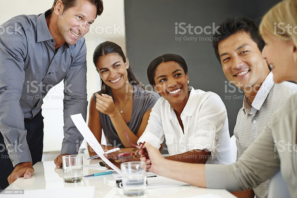 Group of jovial business professionals at a table stock photo