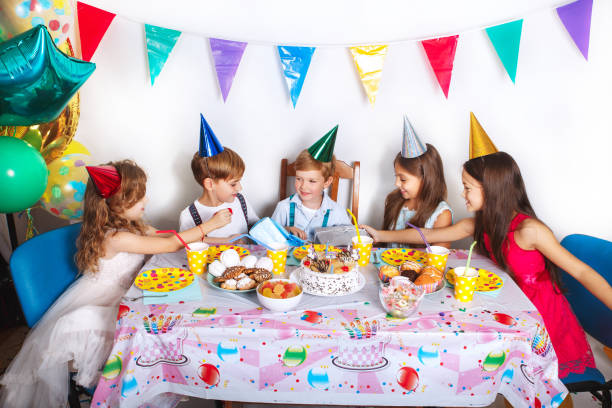 Group of joyful little kids celebrating birthday party at home. Children's funny birthday party in decorated room stock photo