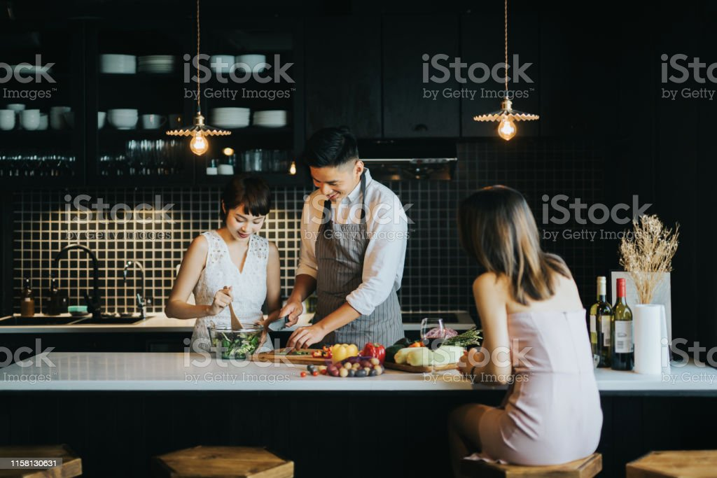 Group of joyful young Asian man and woman cooking together in the kitchen, chatting joyfully and enjoying red wine while preparing food for party Group of joyful young Asian man and woman cooking together in the kitchen, chatting joyfully and enjoying red wine while preparing food for party Adult Stock Photo