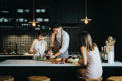 Group Of Joyful Young Asian Man And Woman Cooking Together In The Kitchen Chatting Joyfully And Enjoying Red Wine While Preparing Food For Party Stock Photo - Download Image Now