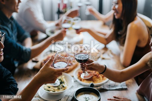 istock Group of joyful young Asian man and woman having fun and toasting with red wine during party 1155378543