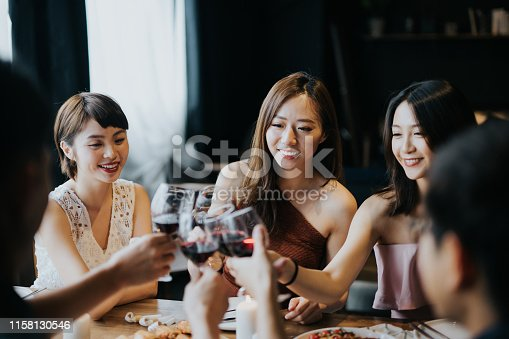 istock Group of joyful young Asian man and woman having fun and toasting with red wine during party 1158130546