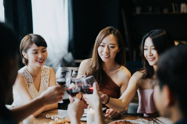 Group of joyful young Asian man and woman having fun and toasting with red wine during party