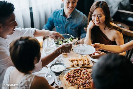istock Group of joyful young Asian man and woman having fun, passing and sharing food across table during party 1155466473