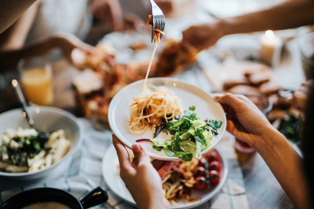 Group of joyful young Asian man and woman having fun, passing and sharing food across table during party Group of joyful young Asian man and woman having fun, passing and sharing food across table during party pasta photos stock pictures, royalty-free photos & images