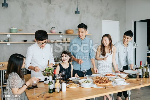 istock Group of joyful young Asian man and woman having fun, passing and sharing food across table during party 1158130577