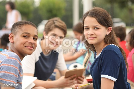 476098743 istock photo Group of junior high school children, teenage friends studying on campus. 1154081633