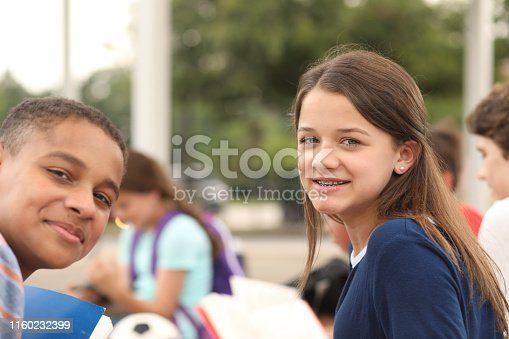 476098743 istock photo Group of junior high school children, teenage friends studying on campus. 1160232399