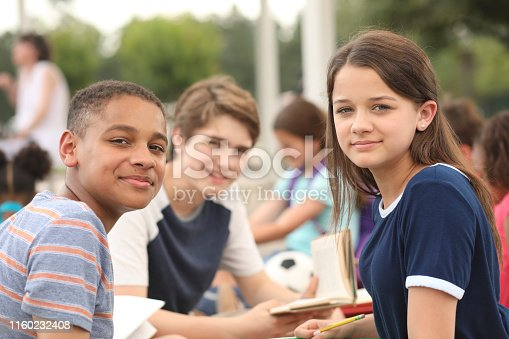 476098743 istock photo Group of junior high school children, teenage friends studying on campus. 1160232408