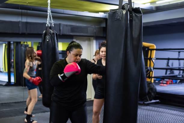 パンチングバッグで練習するキックボクサーのグループ - showus ストックフォトと画像
