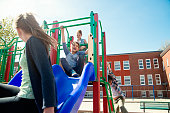 Group of elementary age school children active in playground at recess. Boys and girls aged between 7 and 11 year's old playing on a slide. Very sunny mid-season day. Horizontal full length outdoors shot on a bright sunny day with copy space.