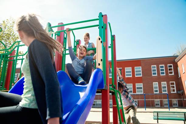 grupo de niños activos en patio de la escuela durante el recreo... - patio de colegio fotografías e imágenes de stock