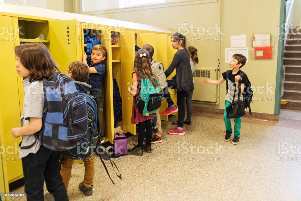 Group of kids around lockers in elementary school. stock photo