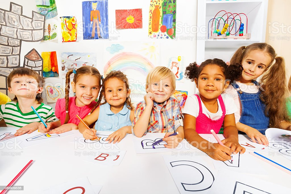 Group of kids, boys and girls in reading class stock photo