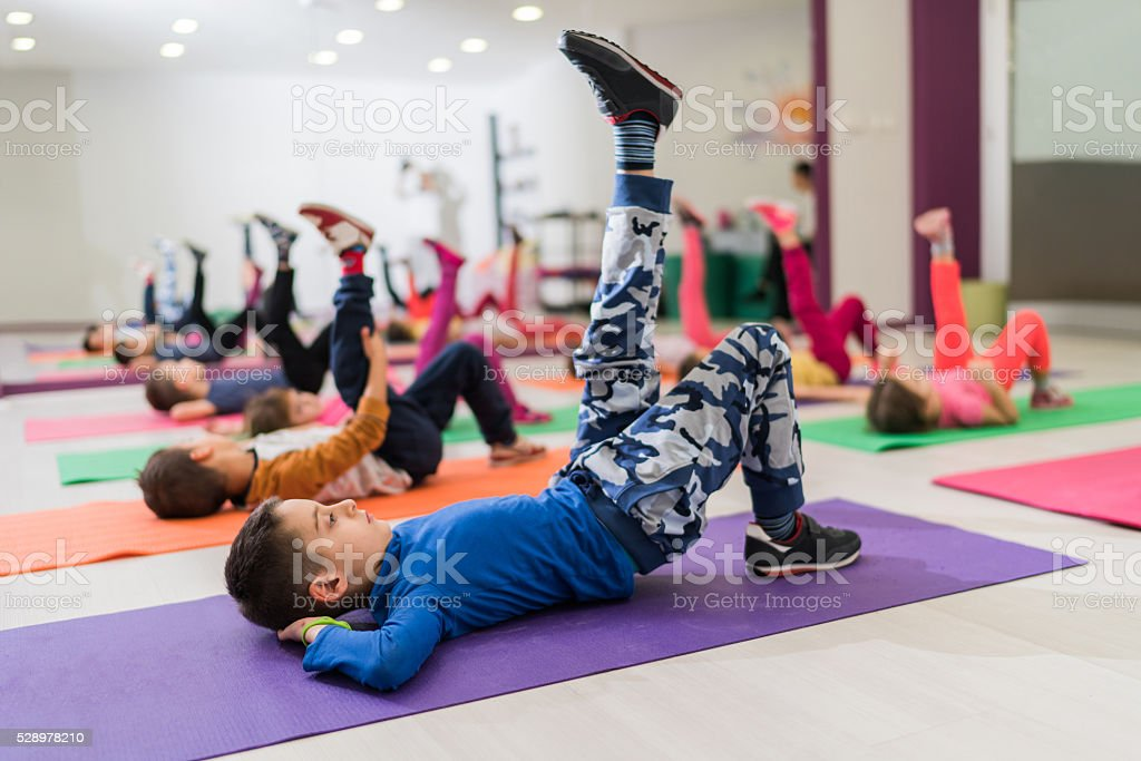 Group of small children having a sports training in a health club and...