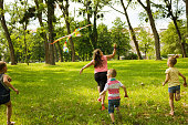 Small children flying a kite and having fun together in nature.