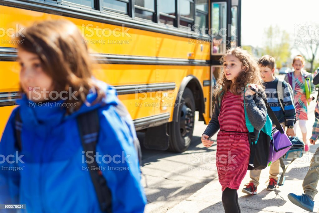 Group of kids getting out of school bus. stock photo