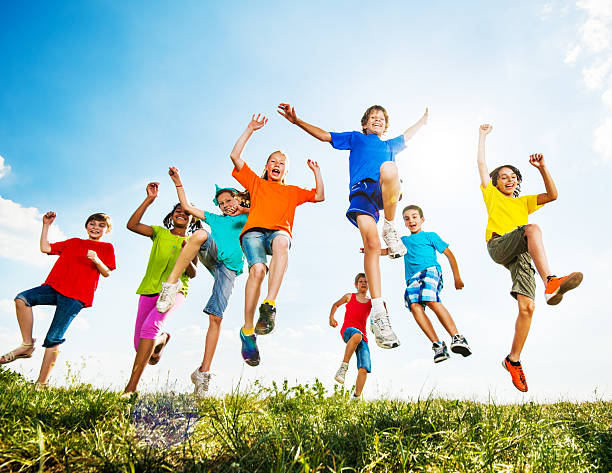 group of kids having fun outdoors. - african youth jumping for joy stock photos and pictures