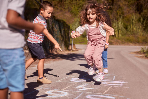 Group of kids having fun playing hopscotch on street stock photo
